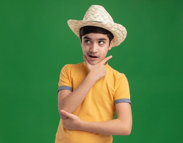 Onder de indruk jonge blanke jongen met een strandhoed die de hand op de kin legt en omhoog kijkt geïsoleerd op een groene muur met kopieerruimte