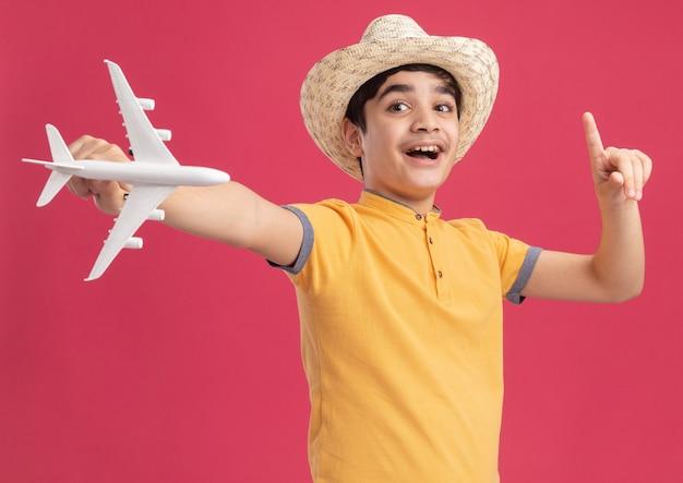 Onder de indruk jonge blanke jongen met een strandhoed die een modelvliegtuig uitrekt en naar de zijkant kijkt