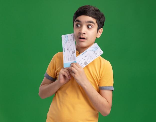 Onder de indruk jonge blanke jongen met vliegtuigkaartjes kijkend naar de zijkant