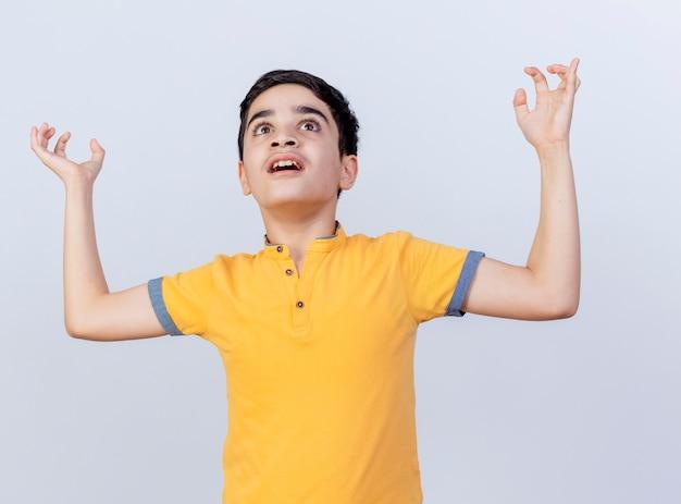 Onder de indruk jonge blanke jongen opzoeken houden handen in de lucht geïsoleerd op een witte achtergrond