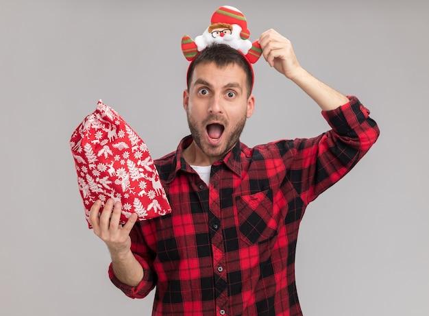 Onder de indruk jonge blanke man met kerst hoofdband houden kerst zak grijpen hoofdband kijken camera geïsoleerd op een witte achtergrond