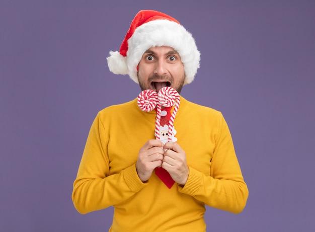 Onder de indruk jonge blanke man met kerstmuts en stropdas houden kerst zoete stokken in de buurt van mond kijken camera klaar om te eten stokken geïsoleerd op paarse achtergrond