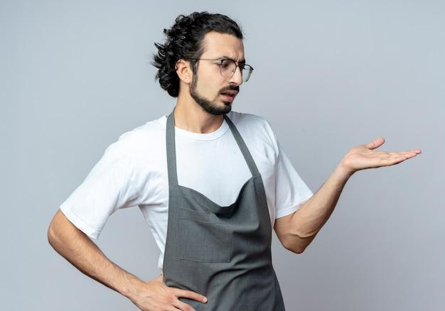 Onder de indruk jonge blanke mannelijke kapper bril en golvende haarband in uniform weergegeven: lege hand en kijken met een andere op taille geïsoleerd op witte achtergrond