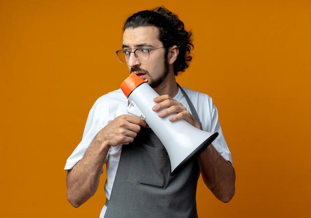 Onder de indruk jonge blanke mannelijke kapper uniform dragen en bril houden spreker en kijken naar kant geïsoleerd op een oranje achtergrond met kopie ruimte