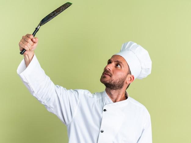 Onder de indruk jonge blanke mannelijke kok in chef-kok uniform en pet verhogen en kijken naar koekenpan