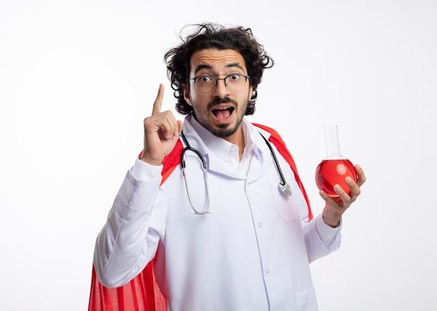 Onder de indruk jonge blanke superheld man in optische bril dragen arts uniform met rode mantel en met stethoscoop om nek houdt rode chemische vloeistof in glazen kolf en wijst omhoog