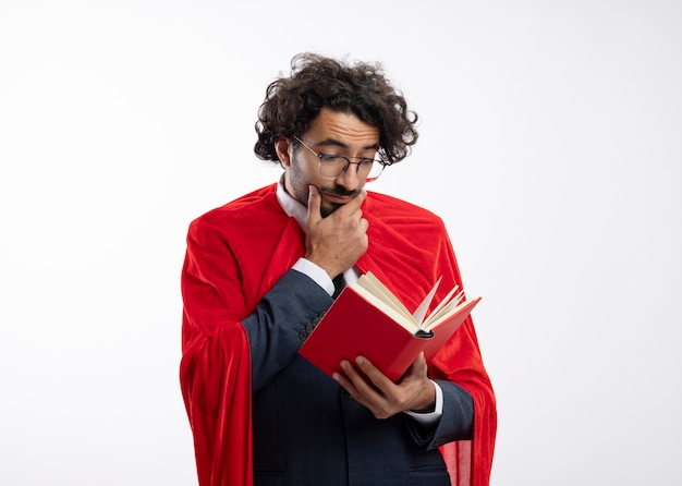 Onder de indruk jonge blanke superheld man in optische bril dragen pak met rode mantel legt hand op kin en leest boek