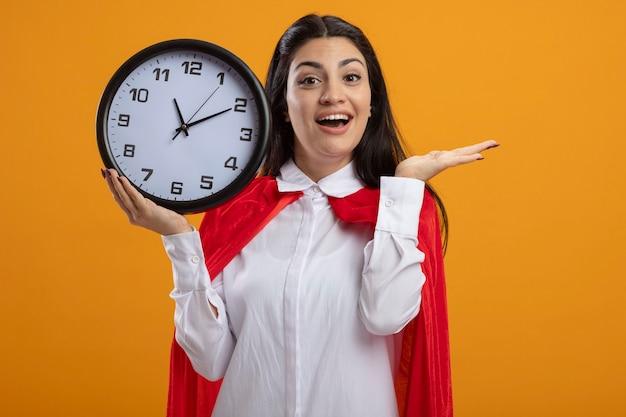 Onder de indruk jonge blanke superheld meisje bedrijf klok kijken camera weergegeven: lege hand geïsoleerd op een oranje achtergrond met kopie ruimte