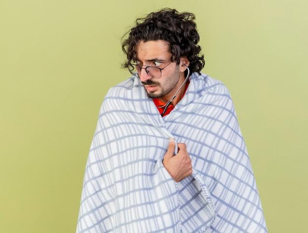Onder de indruk jonge blanke zieke man met bril en stethoscoop gewikkeld in plaid grijpende plaid kijken kant geïsoleerd op olijfgroene achtergrond met kopie ruimte