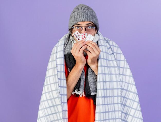 Onder de indruk jonge blanke zieke man met bril, muts en sjaal gewikkeld in geruite bedrijf verpakkingen van medische pillen voor mond geïsoleerd op paarse muur met kopie ruimte