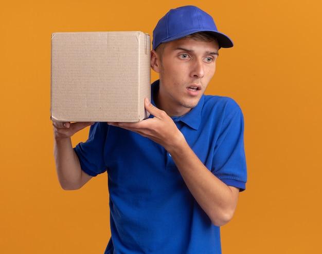 Onder de indruk jonge blonde bezorger houdt de kartonnen doos dicht bij het oor geïsoleerd op een oranje muur met kopieerruimte