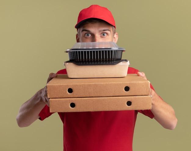 Onder de indruk jonge blonde bezorger houdt voedselpakketten op pizzadozen geïsoleerd op olijfgroene muur met kopieerruimte