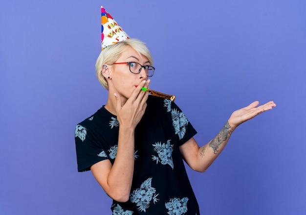Onder de indruk jonge blonde feestvrouw die een bril en een verjaardagspet draagt die de partijblazer blaast die voorzijde bekijkt die lege hand toont die op purpere muur wordt geïsoleerd