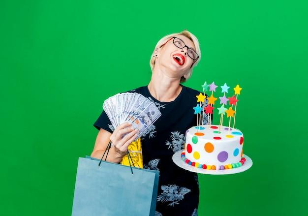 Onder de indruk jonge blonde feestvrouw met bril en verjaardag pet bedrijf verjaardagstaart met sterren geld geschenkdoos en papieren zak opzoeken geïsoleerd op groene muur met kopie ruimte