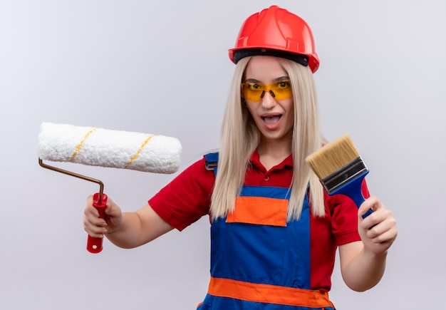 Onder de indruk jonge blonde ingenieur bouwer meisje in uniform dragen veiligheidsbril met kwast en roller op geïsoleerde witte ruimte