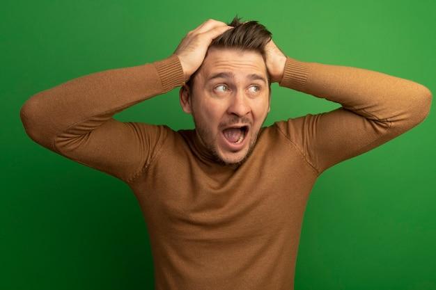 Onder de indruk jonge blonde knappe man die handen op het hoofd zet en naar de kant kijkt die op de groene muur is geïsoleerd