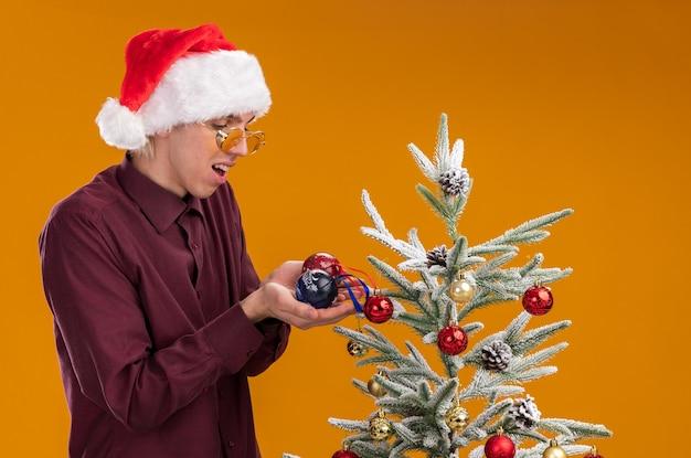 Onder de indruk jonge blonde man met kerstmuts en bril staan in profiel te bekijken in de buurt van versierde kerstboom op oranje achtergrond