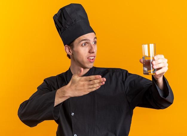 Onder de indruk jonge blonde mannelijke kok in chef-kok uniform en pet kijken naar kant die zich uitstrekt en wijzend op glas water geïsoleerd op oranje muur