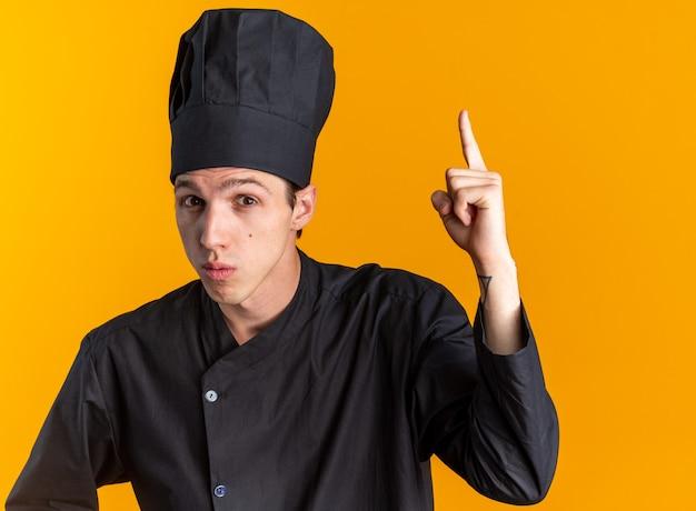 Onder de indruk jonge blonde mannelijke kok in uniform van de chef-kok en pet kijken camera omhoog geïsoleerd op oranje muur