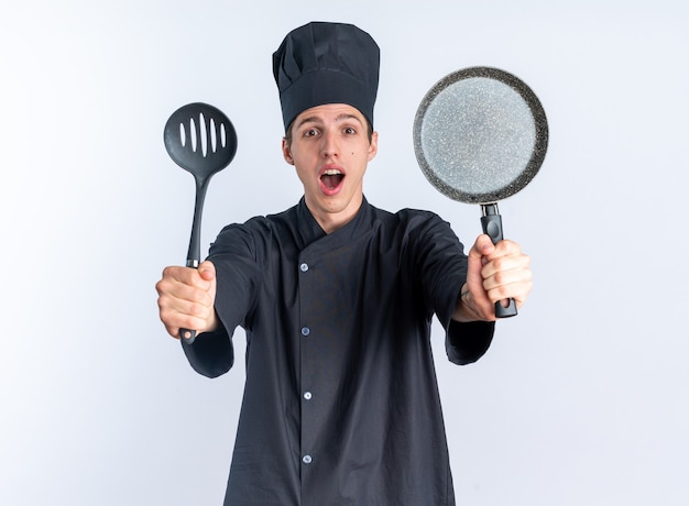 Onder de indruk jonge blonde mannelijke kok in uniform van de chef-kok en pet kijken camera uitrekken spatel en koekenpan naar camera geïsoleerd op witte muur