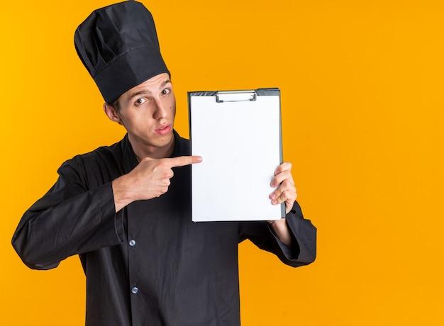 Onder de indruk jonge blonde mannelijke kok in uniform van de chef-kok en pet tonen en wijzend op klembord kijken camera geïsoleerd op oranje muur met kopie ruimte