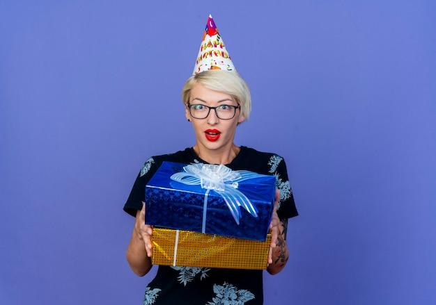 Onder de indruk jonge blonde partijvrouw die glazen en verjaardag glb draagt die giftdozen houdt die voorzijde bekijkt die op purpere muur wordt geïsoleerd