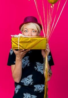 Onder de indruk jonge blonde partijvrouw die partijhoed draagt die giftdoos en ballons houdt die voorzijde van achter giftdoos bekijken die op roze muur wordt geïsoleerd