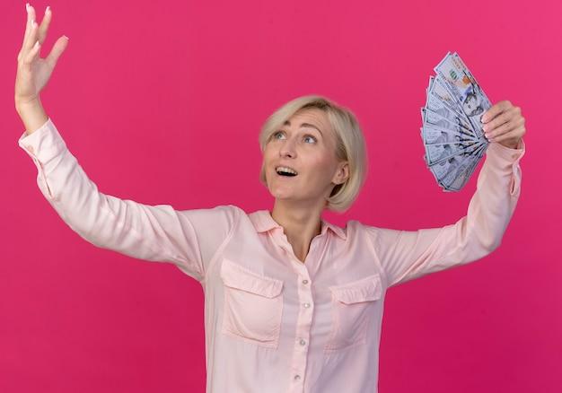 Onder de indruk jonge blonde slavische vrouw die geld en hand opheft en bekijkt die op roze achtergrond wordt geïsoleerd
