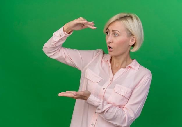 Onder de indruk jonge blonde slavische vrouw die kant bekijkt en grootte toont die op groene achtergrond met exemplaarruimte wordt geïsoleerd