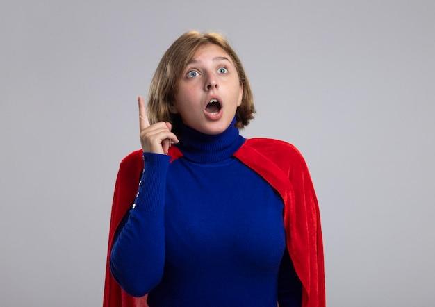 Onder de indruk jonge blonde superheld vrouw in rode cape op zoek recht omhoog geïsoleerd op een witte muur met kopie ruimte