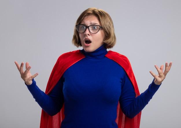 Onder de indruk jonge blonde supervrouw in rode cape die glazen draagt die kant houden dient lucht in die op witte muur wordt geïsoleerd