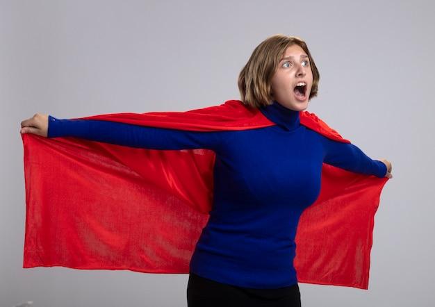 Onder de indruk jonge blonde supervrouw in rode cape die haar heldencape grijpt die recht kijkt alsof vliegend op een witte muur wordt geïsoleerd