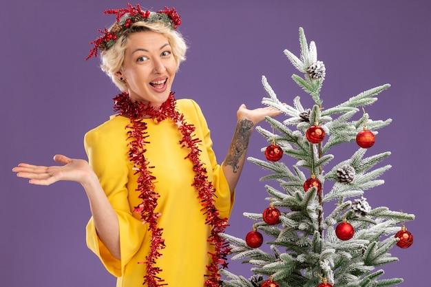 Onder de indruk jonge blonde vrouw die de kroon van kerstmis en klatergoudslinger om hals draagt die zich dichtbij versierde kerstboom bevindt die camera bekijkt die lege handen toont die op purpere achtergrond wordt geïsoleerd