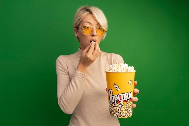 Onder de indruk jonge blonde vrouw die een zonnebril draagt met een emmer popcorn en popcornstukken in de buurt van de mond en kijkt naar de zijkant geïsoleerd op een groene muur met kopieerruimte