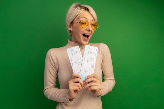 Onder de indruk jonge blonde vrouw met een zonnebril die vliegtuigtickets vasthoudt en bekijkt en kijkt naar de voorkant geïsoleerd op een groene muur met kopieerruimte