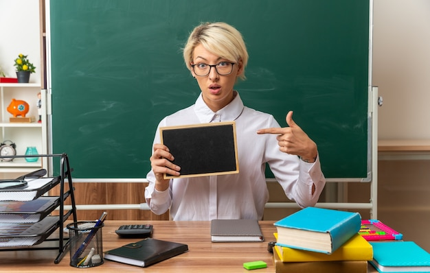 Onder de indruk jonge blonde vrouwelijke leraar met een bril die aan een bureau zit met schoolhulpmiddelen in de klas die naar een mini-bord kijkt en naar de camera wijst