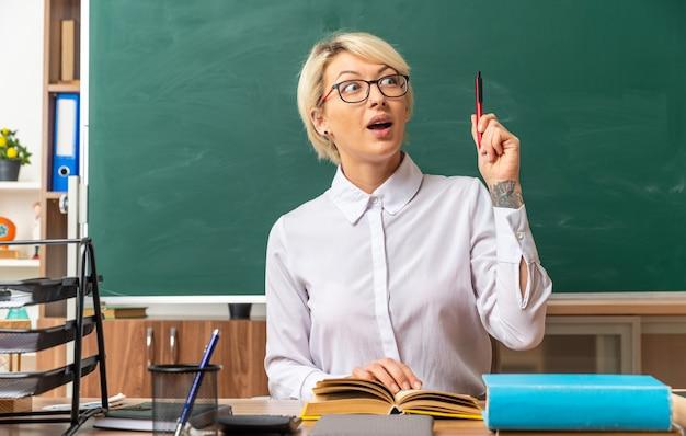 Onder de indruk jonge blonde vrouwelijke leraar met een bril die aan het bureau zit met schoolhulpmiddelen in de klas en omhoog wijst met de pen die de hand op het open boek houdt en naar de zijkant kijkt