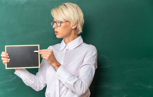 Onder de indruk jonge blonde vrouwelijke leraar met een bril in de klas staan voor schoolbord met mini schoolbord kijken ernaar wijzend met krijt met kopieerruimte