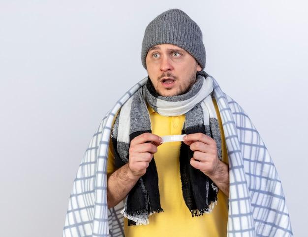 Onder de indruk jonge blonde zieke slavische man met muts en sjaal gewikkeld in plaid houdt medische gips geïsoleerd op een witte muur met kopie ruimte