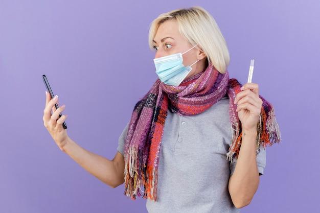 Onder de indruk jonge blonde zieke vrouw die medische masker en sjaal draagt, houdt thermometer vast en kijkt naar telefoon die op paarse muur wordt geïsoleerd