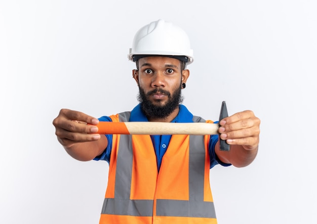 Onder de indruk jonge bouwer man in uniform met veiligheidshelm met hamer geïsoleerd op een witte muur met kopie ruimte
