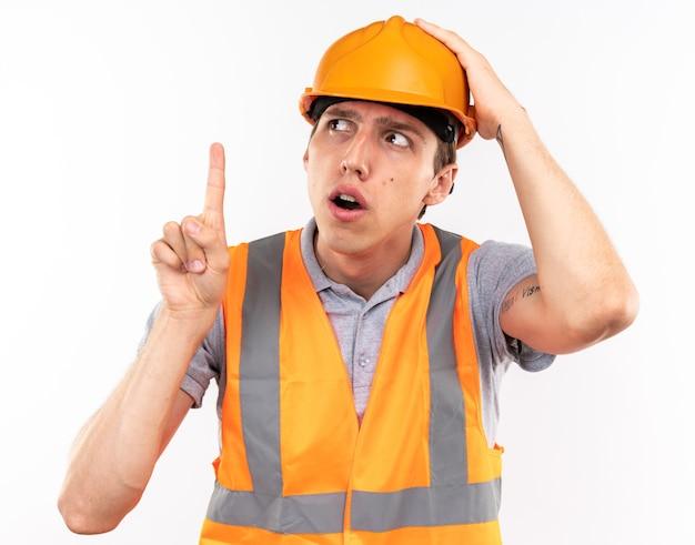 Onder de indruk jonge bouwer man in uniform wijst naar omhoog geïsoleerd op een witte muur