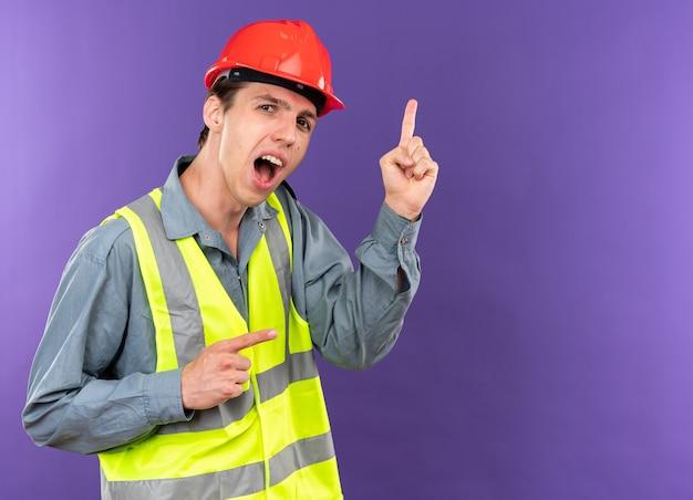 Onder de indruk jonge bouwer man in uniforme punten aan de zijkant geïsoleerd op blauwe muur met kopieerruimte