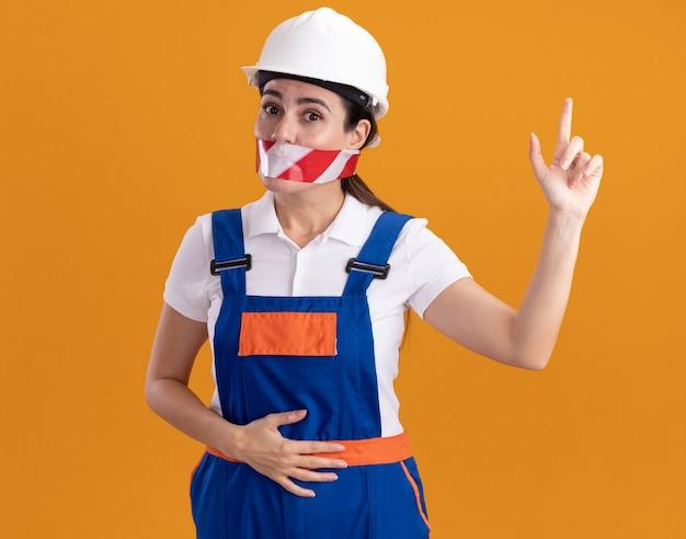 Onder de indruk jonge bouwersvrouw in uniform verzegelde mond met ducttape wijst naar omhoog geïsoleerd op oranje muur