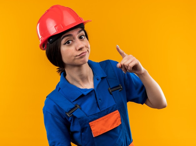 Onder de indruk jonge bouwvrouw in uniform wijst naar de camera