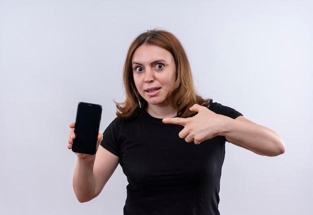 Onder de indruk jonge casual vrouw die mobiele telefoon houdt en erop wijst op geïsoleerde witte ruimte