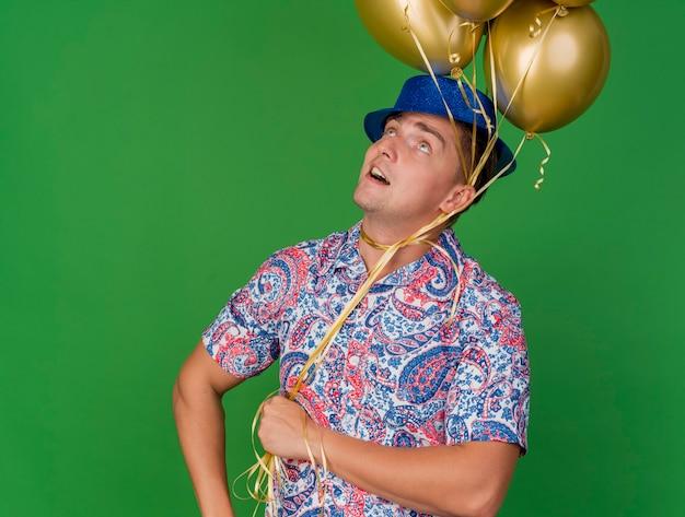 Onder de indruk jonge feest man opzoeken dragen blauwe hoed met ballonnen om nek geïsoleerd op groen