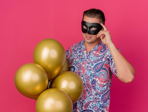 Onder de indruk jonge feestmens die een maskerade-oogmasker draagt dat ballonnen vasthoudt en de vinger op de tempel legt die op roze wordt geïsoleerd