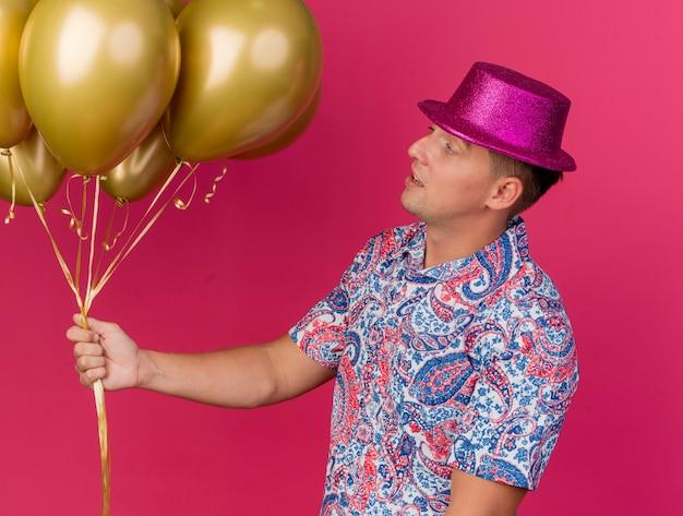 Onder de indruk jonge feestmens die een roze hoed draagt en naar ballonnen kijkt die op roze worden geïsoleerd