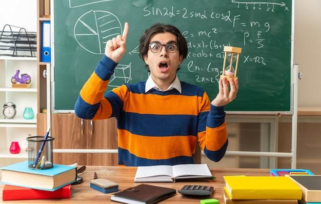 Onder de indruk jonge geometrieleraar met een bril die aan het bureau zit met schoolbenodigdheden in de klas met een zandloper die naar de voorkant kijkt en omhoog wijst